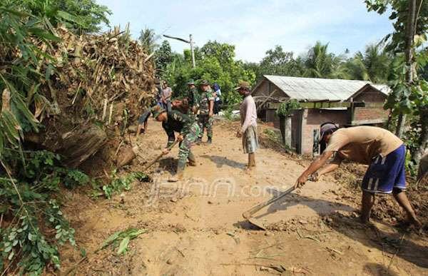 GOTONG ROYONG: Personel TNI dan warga membersihkan tebing yang longsor di Mojo, Kediri (17/12)