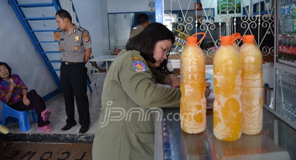 Petugas menyita miras oplosan. Foto: dok.JPNN
