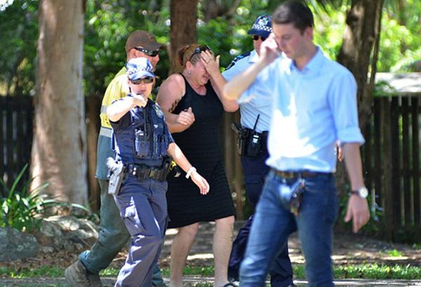 Polisi menghibur seorang wanita yang diduga mengalami depresi terkait tragedi berdarah di Kota Cairns, Negara Bagian Queensland, Australia. Foto: Daily Mail