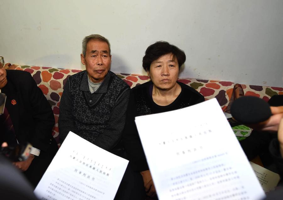 Orangtua Hugjiltu, Li Sanren (kiri) dan Shang Aiyun, saat hendak menerima dokumen hukum anaknya, di pengadilan ulang di Hohhot, Tiongkok, Senin (15/12). Foto: Xinhua
