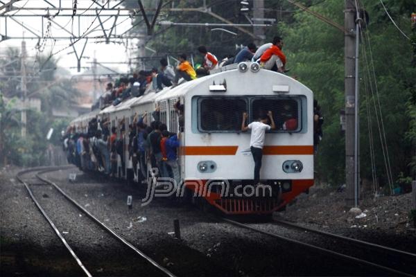 Penumpang KRL membeludak hingga ke atas gerbong