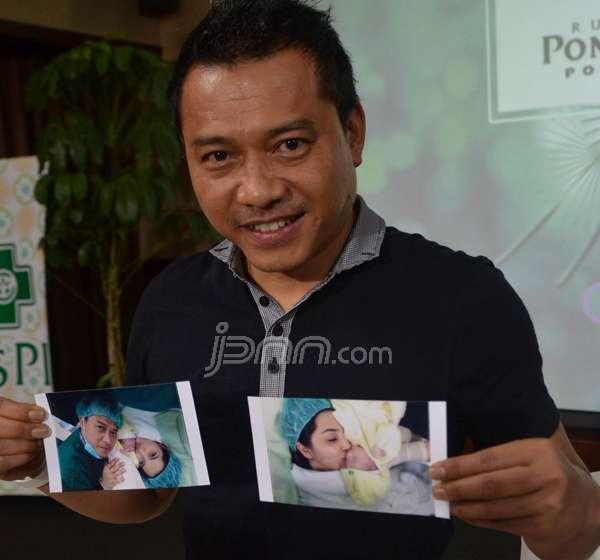 Anang menunjukan foto istrinya usai melahirkan saat konferensi pers, Minggu (14/12).