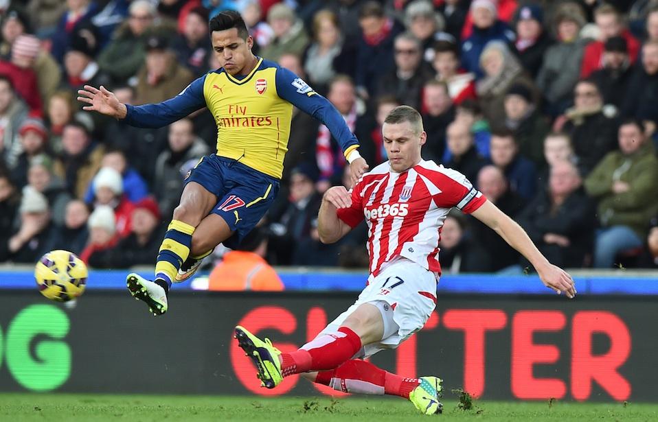 Alexis Sanchez beraksi melewati pemain Stoke City. FOTO: AFP