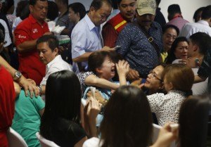 Family members of passengers onboard AirAsia flight QZ8501 react at a waiting area in Juanda International Airport