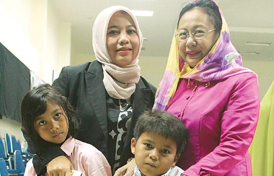 BAHAGIA: Sulastri bersama dua anaknya, Syifa Puan Nouri, 8, dan Syamil Aulia Rahman, 6, berfoto dengan Rekaveny, istri Wakil Gubernur Kepri Soerya Respationo. (Ariski Prasetyo/Jawa Pos)