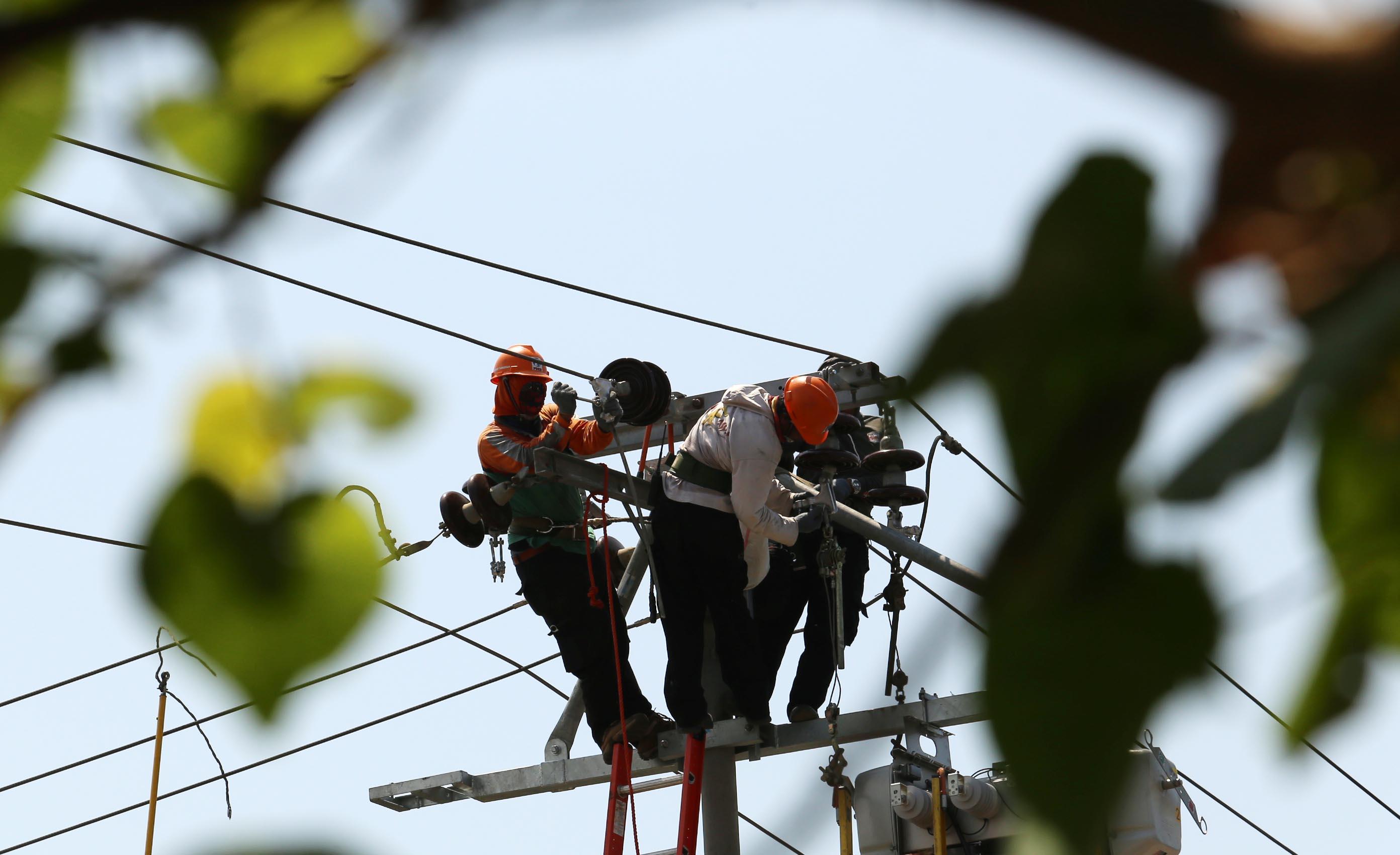 FLUKTUATIF : Petugas PLN Makassar melakukan penggantian suku cadang jaringan listrik yang rusak di Jalan Kakatua, Makassar, Sulsel, 20 November lalu. (Muhammad I Ama/Fajar/JPNN)