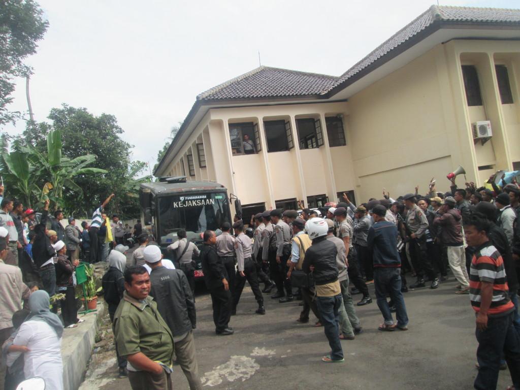TUNTUTAN: Tampak aparat Kepolisian menjaga warga yang memaksa sopir bus Kejaksaan pembawa terdakwa tiga warga untuk dibebaskan. foto : arif