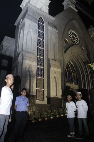 Pemuda masjid menjaga gereja di Ambon saat malam natal, Rabu (24/12).