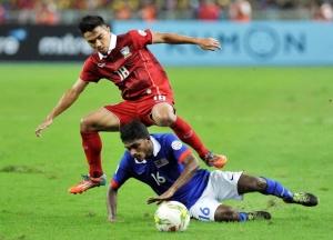 Pemain Thailand, Chanatip Songkrasin (merah) berebut bola dengan pemain Malaysia, S.Kunalan dalam final Suzuki Cup di Stadion Bukit Jalil Stadium, Kuala Lumpur, Sabtu malam.  Foto: Bernama