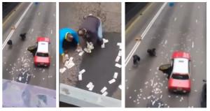 Pengguna jalan memungut uang yang bertebaran di jalanan