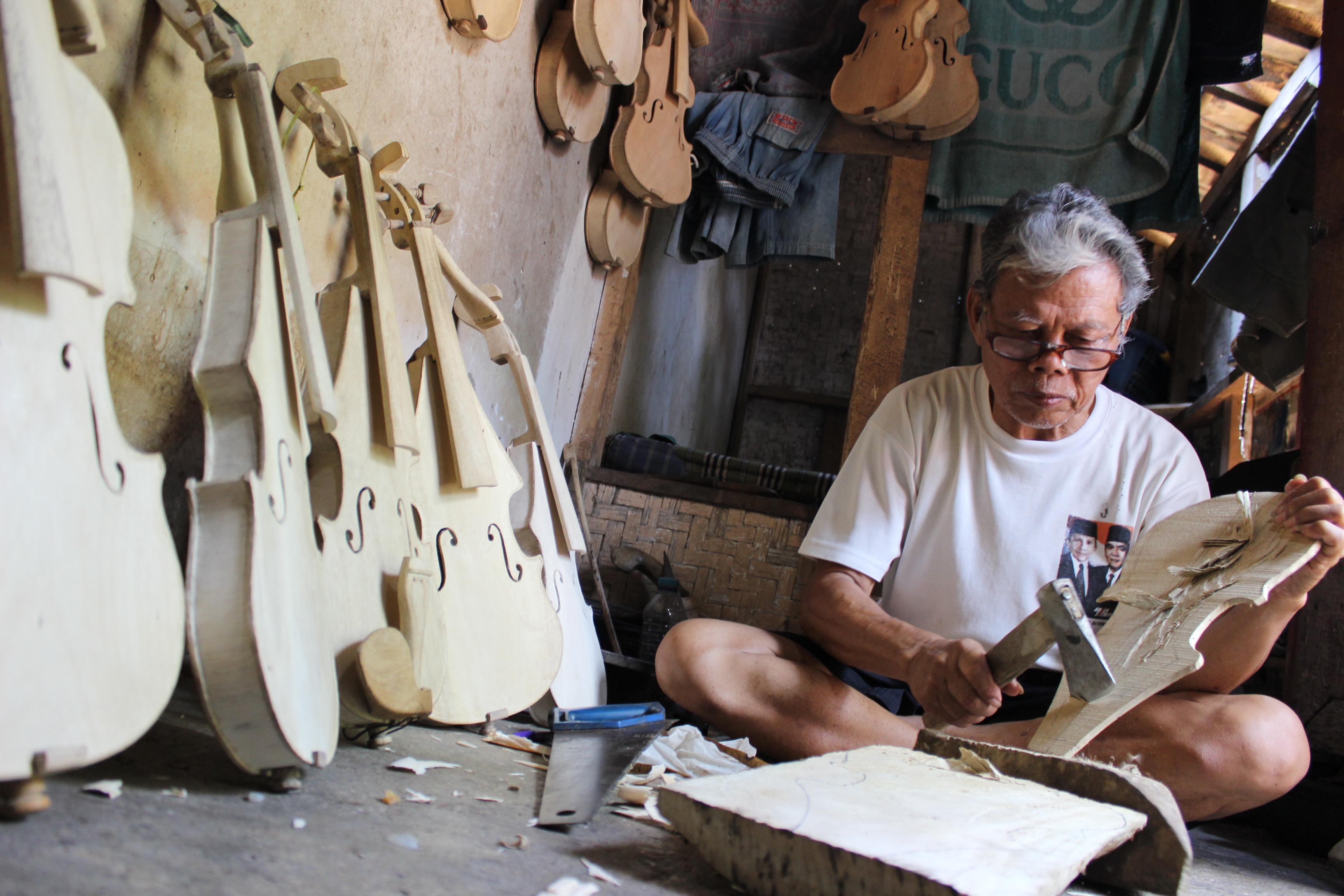 Mustofa sedang membuat biola. Foto Guruh/pojoksatu.id