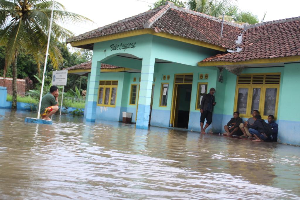 BANJIR : Sejumlah aparatur Desa Babakancaringin Kecamatan Karantengah Cianjur hanya bisa termangu saat bangunan bale desa digenangi air. foto : arif mulyana