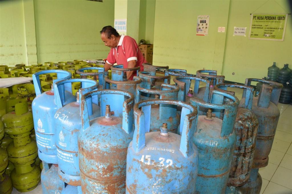 TAK LAKU : Pemilik agen gas elpiji perlihatkan gas 12 kg yang kini ditinggalkan pembeli akibat naik secara perlahan. foto : farhan
