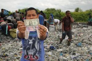 Salah seorang warga kampung Parung Dengek, desa Wana Herang, Kec. Gunung Puti, Bogor, Jawa Barat menunjukkan dollar yang berhasil didapatkannya dalam tumpukan sampah di TPS PT. Samba Paper.