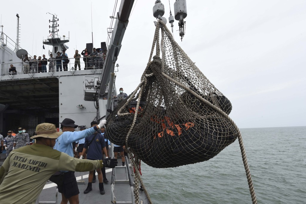 Personnel on the Indonesian Navy vessel KRI Banda Aceh lift body bags containing dead bodies recovered during a search operation for passengers of AirAsia flight QZ8501, at sea