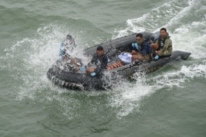 Indonesian Navy frogmen and underwater demolition unit personnel on a boat carrying body bags containing dead bodies from AirAsia flight QZ8501, are seen as bodies are lifted to the Indonesian Navy vessel KRI Banda Aceh, at sea