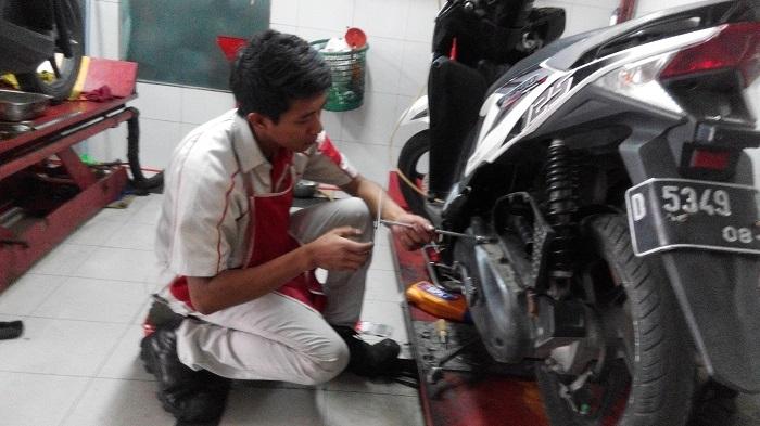 Seorang mekanik sedang melakukan service rutin sepeda motor Honda milik konsumen. (FOTO : Asep/Pojoksatu)