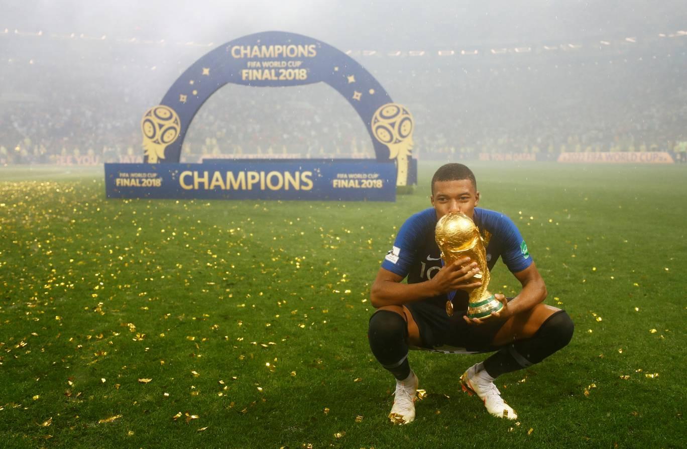 Striker muda Prancis, Kylian Mbappe mencium trofi Piala Dunia 2018 (as.com)