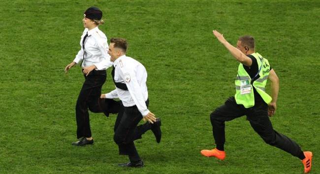 Petugas keamanan mengejar dua orang penyusup yang masuk ke lapangan saat laga final Piala Dunia 2018 (standard.co.uk)