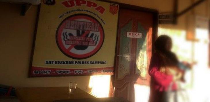Keluarga M berdiri di depan ruang UPPA Polres Sampang. (Moh Iqbal/RadarMadura.id)