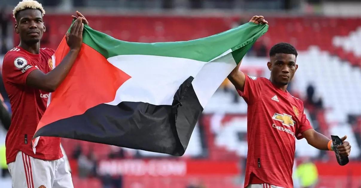 Paul Pogba kibarkan bendera Palestina bersama Amad Diallo usai laga MU vs Fulham di Old Trafford, Rabu (19/5/2021) dini hari. Foto: Foto: Laurence Griffiths/POOL/AFP/France24