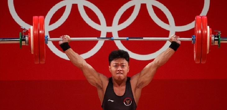 Lifter Indonesia Rahmat Erwin Abdullah melakukan angkatan di Olimpiade Tokyo 2020 di Tokyo International Forum, Tokyo, Jepang, Rabu (28/7). Foto: Chris Graythen/Getty Images