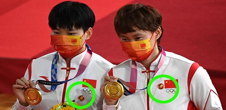 Atlet sepeda China Bao Shanju dan Zhong Tianshi mengenakan pin berlogo pendiri partai komunis Mao Zedong.